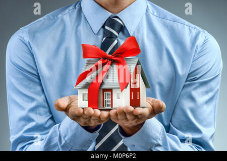 Travailleur en chemise bleue holding house avec ruban rouge. Close up. Concept d'affaires Banque D'Images