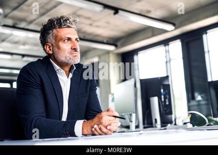 Mature businessman in office penser Banque D'Images