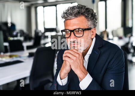 Portrait of serious businessman wearing glasses in office Banque D'Images