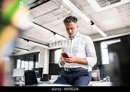 Mature businessman using cell phone in office Banque D'Images
