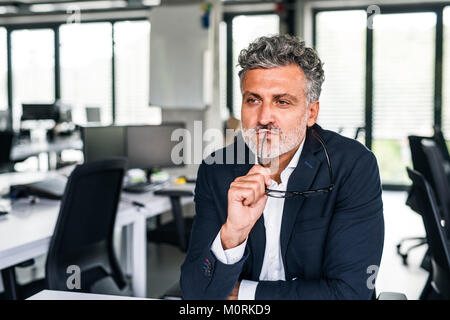 Portrait of serious mature businessman in office penser Banque D'Images