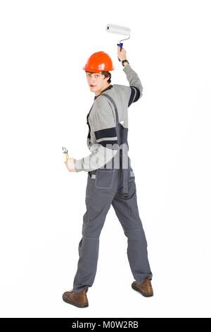 Un jeune homme en habits gris de casque et orange de peindre les murs dans la chambre. Banque D'Images