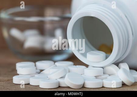 Comprimés en médecine bouteilles sur fond de bois Banque D'Images