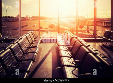 Des sièges vides dans un aéroport hall de départ au coucher du soleil, aux teintes de couleur photo, voyages et transport concept.