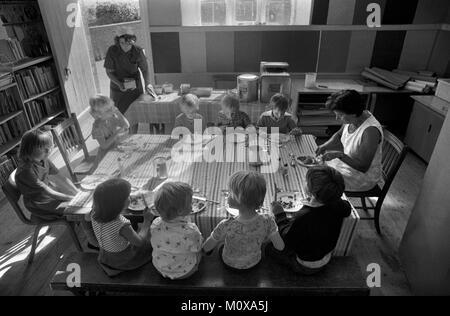 Village primaire années 1970 Angleterre. Les enfants de l'école s'assoient ensemble à une table avec un membre du Banque D'Images