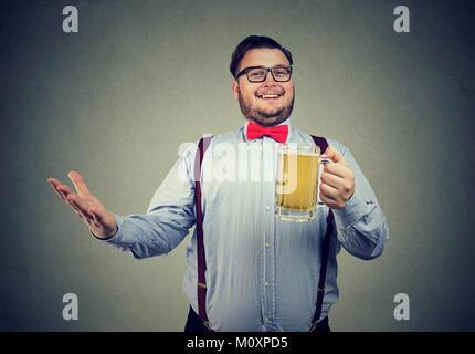 L'homme trapu en tenue officielle et les lunettes posant joyeusement à huis clos tenue mug de bière. Banque D'Images