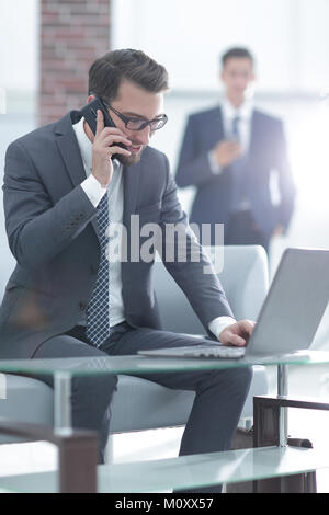 Portrait of businessman talking on mobile phone in office Banque D'Images
