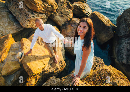 Caucasian couple climbing on rocks at beach Banque D'Images