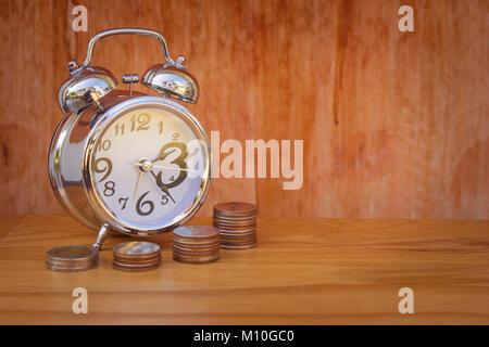 Le temps est argent Concept: Réveil mis sur table en bois avec pile de pièces de monnaie en argent (baht) en premier Banque D'Images