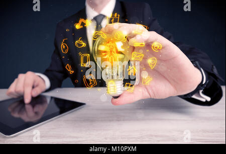 Un bureau commercial promouvoir ses idées de concept avec l'illustration des médias en ligne et les logos de l'appareil autour de l'ampoule en verre électrique.