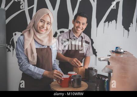 Portraif de deux hommes et femmes cafe owner occupé à travailler dans leur café-restaurant Banque D'Images