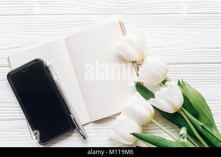 Écran de téléphone portable et élégant stylo et tulipes sur fond rustique en bois blanc. Télévision avec fleurs Banque D'Images