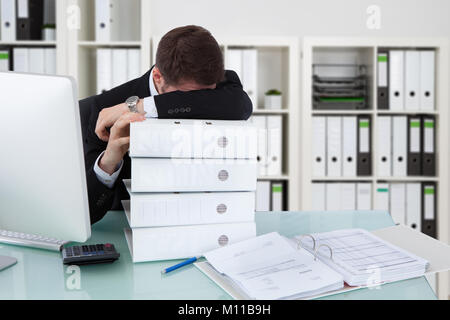 Businessman Sleeping On Stack Of Folders In Office Banque D'Images