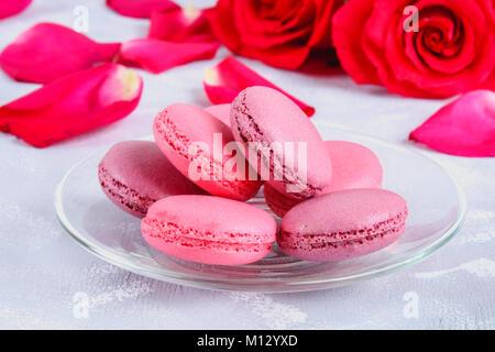 Macarons roses et mauves sur un tableau gris entouré de fleurs roses et blanches Banque D'Images