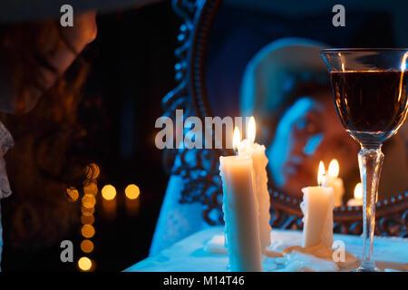 Visage de femme trouble miroir avec bougies et vin rouge Banque D'Images