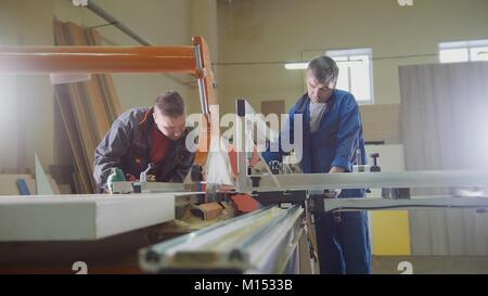 Les hommes - les charpentiers sont la coupe de bois sur scie électrique à l'usine de meubles Banque D'Images
