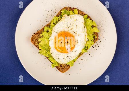 Œuf frit avant la fin de l'avocat écrasé et le pain de seigle Sandwich ouverte sur un fond bleu Banque D'Images