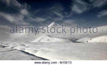 Un couvert de neige et misty Rannoch Moor en regardant vers la montagne Blackmount avec deux skieurs dans la distance il y en haut de la colline. Glen