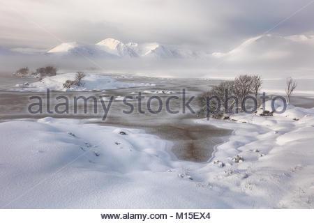 Un couvert de neige Rannoch Moor à plus d'un frozen Lochan na h-achlaise au misty mountain range. Blackmount Glencoe, Ecosse