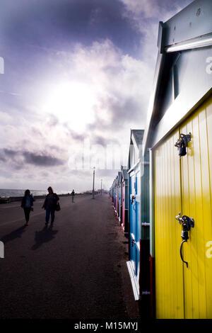 La plage de Brighton, promenade sur la droite une rangée de cabines colorées allant de grande ou petite et la distance Banque D'Images