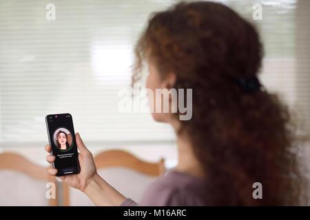 Femme avec Apple iPhone X smartphone dans sa main grâce à l'authentification biométrique, ID app Banque D'Images