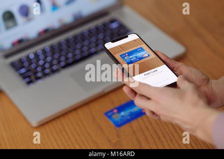 Femme avec iPhone X smartphone dans sa main la numérisation d'une carte de crédit avec Apple, Apple paie Wallet Banque D'Images