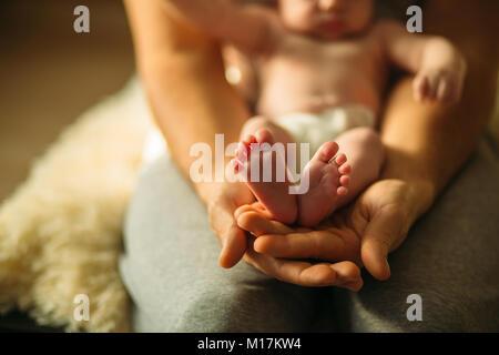 Bébé nouveau-né dans les jambes de Belles Mères part avec soft focus sur le pied d'babie