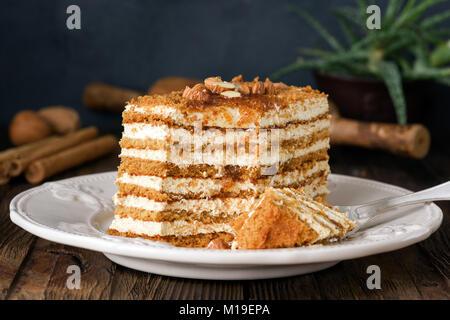 Gâteau au miel avec des amandes sur plaque blanche. Gâteau russe Medovik Banque D'Images