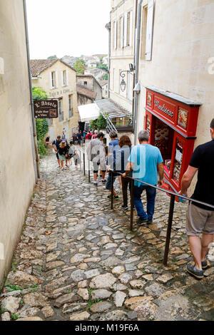 Groupe de personnes marchant dans la Rue de cailloux glissants du Tertre de la Tente à Saint-Emilion, un village Banque D'Images