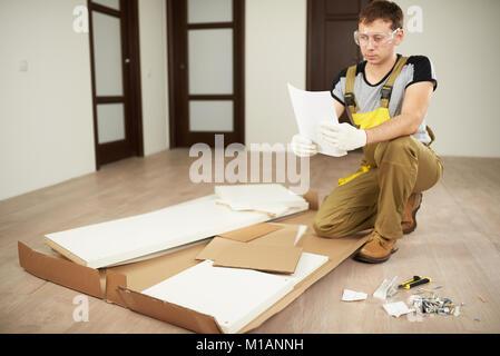 Meubles installer travailleur avec l'enseignement. Les travaux de réparation à plat. De l'aide professionnelle à Banque D'Images