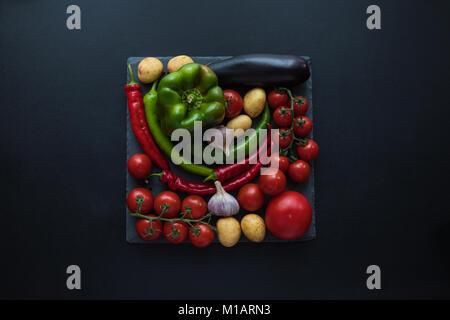 Vue de dessus les tomates mûres fraîches, poivrons, l'ail, l'aubergine et les pommes de terre sur le bord de l'ardoise Banque D'Images