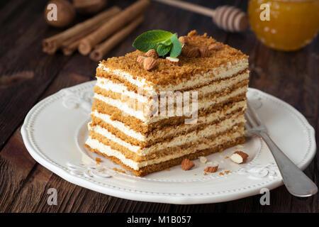 Tranche de gâteau de miel en couches le russe Medovik décoré avec des amandes et menthe on white plate Banque D'Images