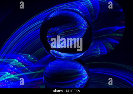 Light painting avec une boule de cristal placé sur une surface en verre et à l'aide de LED lumineuses colorées comme Banque D'Images