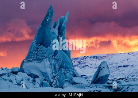 Un iceberg bleu pointues au coucher du soleil à Jokulsarlon Lagoon dans le sud de l'Islande Banque D'Images