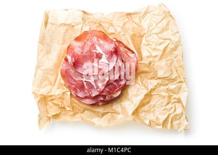 Tranches de jambon de pays sur papier isolé sur fond blanc. Banque D'Images