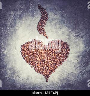 Forme de coeur à partir de grains de café torréfiés à la vapeur sur un fond noir en violet aux tons rustiques vintage Banque D'Images