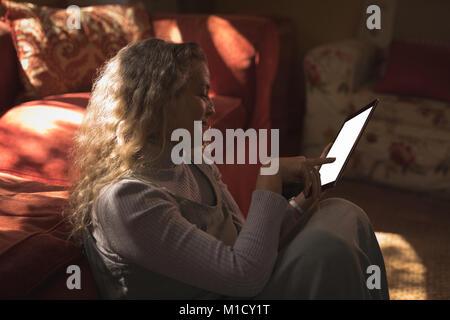 Young woman sur le sol et en utilisant son tablet Banque D'Images