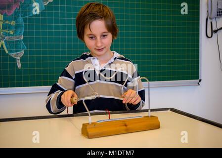 Un garçon mène une expérience de l'électricité avec une tige Banque D'Images