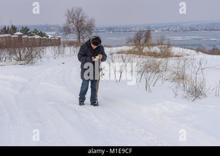 Contrôle de l'homme mature téléphone cellulaire pendant qu'ils marchaient sur une route enneigée près de frozen Banque D'Images