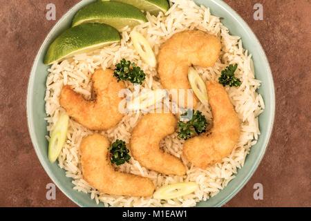Sauté de crevettes tempura à la japonaise avec du riz dans un bol contre un arrière-plan de tuile rouge Banque D'Images