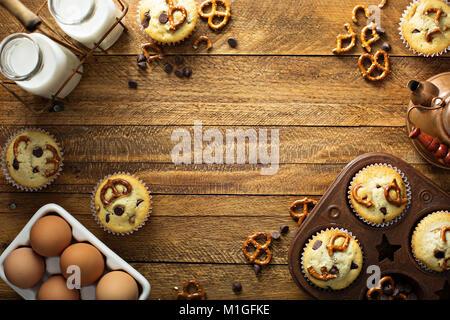 Muffins aux pépites de chocolat au lait et de bretzel sur fond de bois frais généraux pour le dessert tourné with Banque D'Images