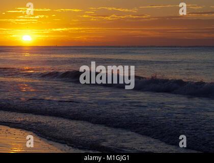 Lever du soleil au-dessus des vagues se brisant sur beach