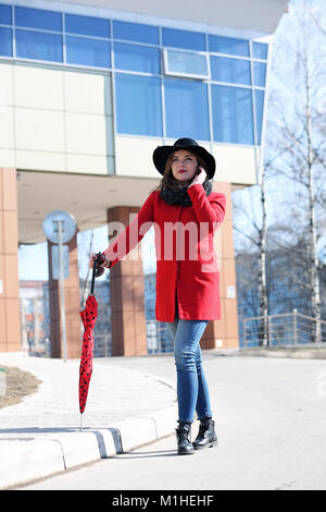 Cute businesswoman dans un manteau rouge sur un fond de verre Banque D'Images