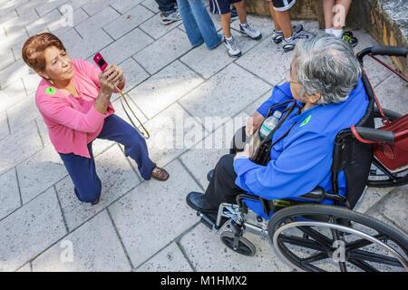 Hispanic woman téléphone appareil photo prend photo mère âgées handicapées en fauteuil roulant Banque D'Images