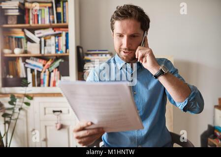 La lecture de l'homme par les formalités administratives et de l'utilisation d'un cellulaire à la maison Banque D'Images