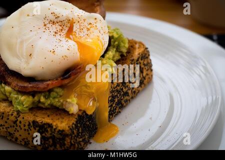 L'avocat sur des toasts avec du bacon et œuf poché Banque D'Images