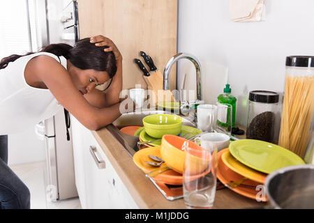 L'accent sur les jeunes African Woman Leaning près de l'évier de cuisine à la recherche d'ustensiles de cuisine Banque D'Images