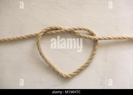 Forme de coeur faits de corde sur fond de bois blanc Banque D'Images