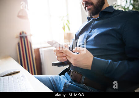 Man in wheelchair with smartphone dans son bureau. Banque D'Images