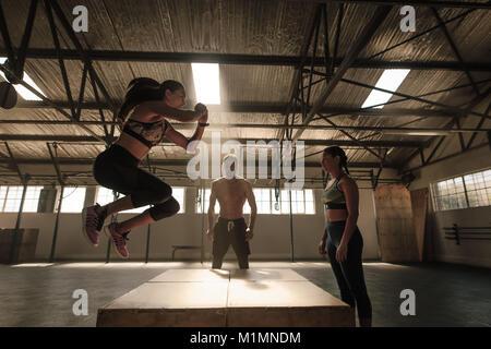 Femme sautant sur boîte en bois, guidé par le formateur. Les jeunes dans l'exécution de routine d'entraînement de Banque D'Images